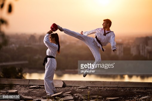 Martial artist fighter exercising with female partner at sunset.