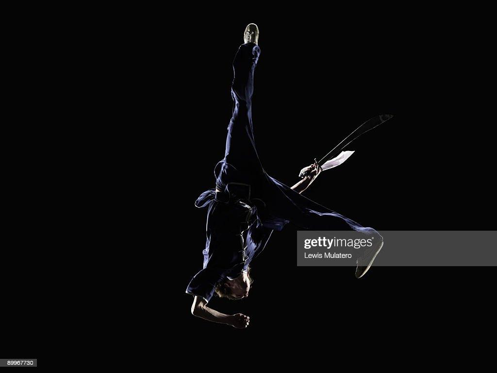 Martial artist in aerial position with broadsword : Foto de stock