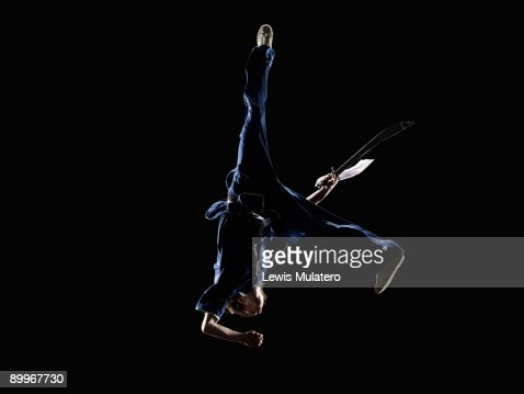 Martial artist in aerial position with broadsword