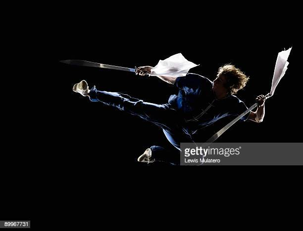 Martial artist jumping kick with double swords