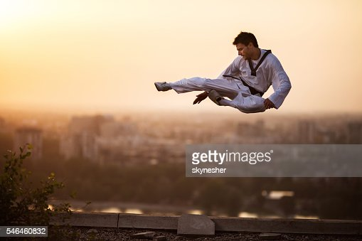 Martial artist performing high kick in mid air at sunset.