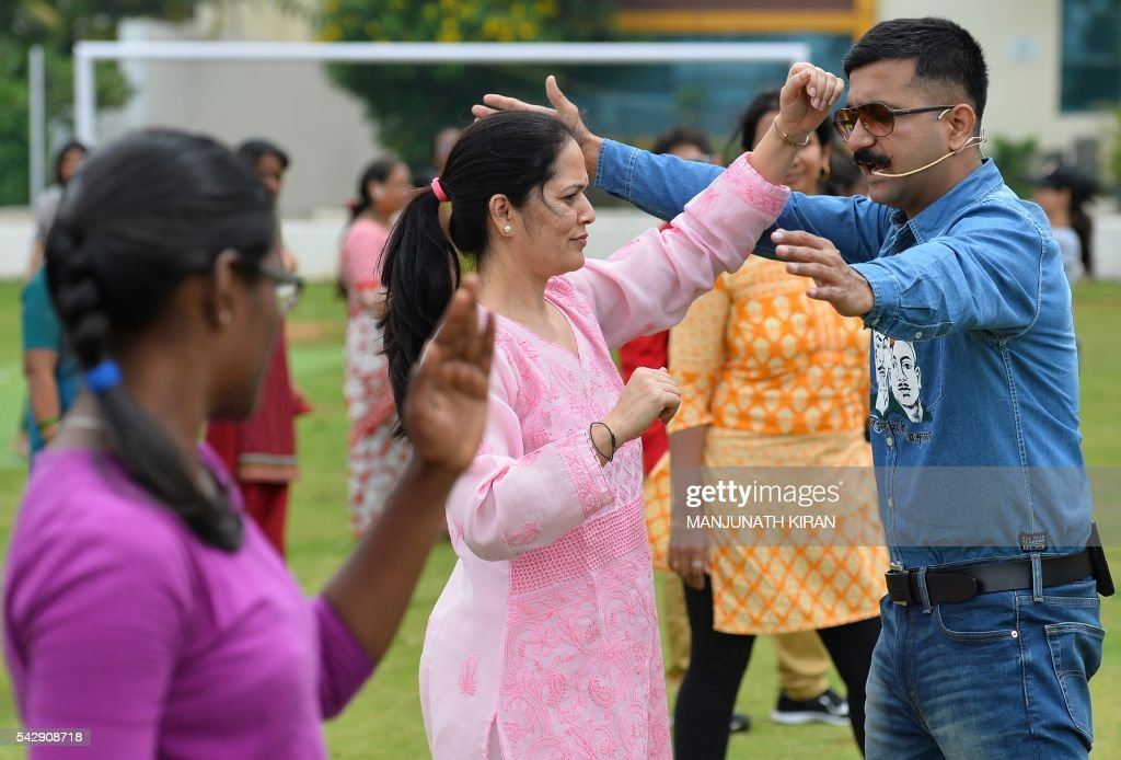 Martial Arts instructor and Commando trainer in the Indian armed forces Shifuji Shaurya Bharadwaj (R) gives instructions during an unarmed combat and self-discipline class held as part of a training program for women in Bangalore on June 25, 2016. / AFP / Manjunath Kiran