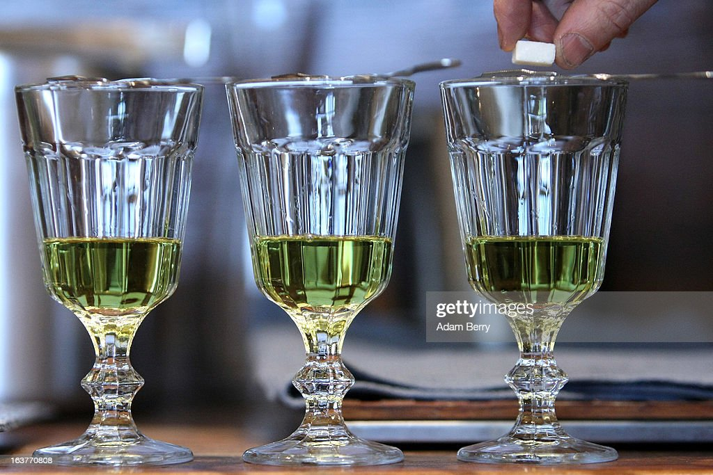 Martial Philippi owner of the Absinth Depot shop places a sugar cube onto an absinthe spoon atop a glass of absinthe on March 15 2013 in Berlin...
