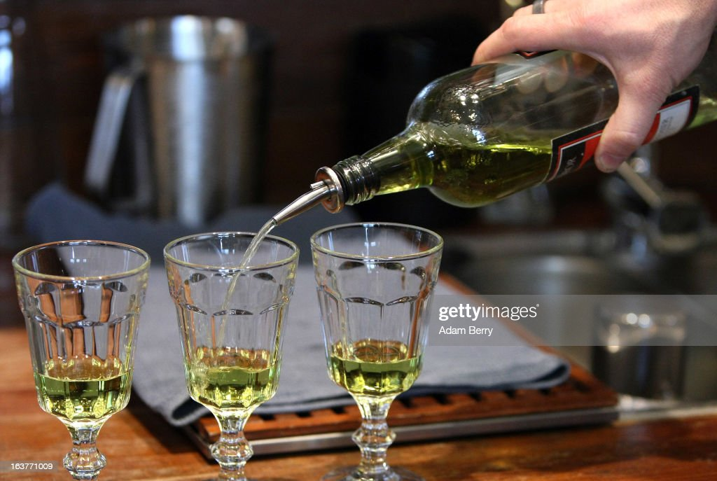 Martial Philippi owner of the Absinth Depot shop pours absinthe into glasses on March 15 2013 in Berlin Germany The highly alcoholic drink absinthe...