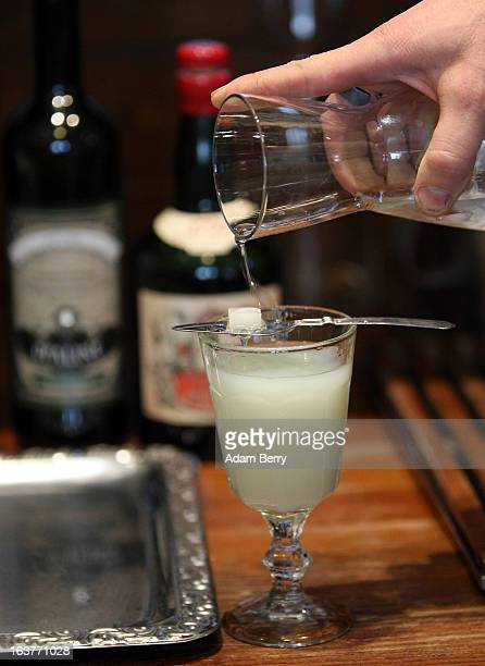 Martial Philippi owner of the Absinth Depot shop pours water through a sugar cube sitting on an absinthe spoon into a glass of absinthe on March 15...