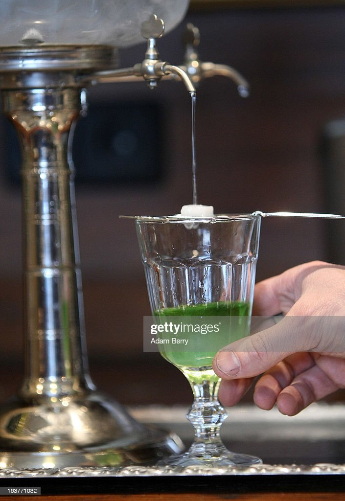 Martial Philippi, owner of the Absinth Depot shop, uses an absinthe fountain to pour water through a sugar cube atop an absinthe spoon sitting on a glass of absinthe on March 15, 2013 in Berlin, Germany. The highly alcoholic drink absinthe was banned in much of Europe during World War I, and only in recent years became once again legal, finding its way back into bars and shops. Meanwhile the European Parliament is divided on its vote on the European Commission's attempt to standardize the definition of the drink by deciding if and how much of the two substances anethole and the chemical thujone, a toxin extracted from wormwood, which has given the drink its reputation for producing mind-altering effects, must be contained within it to officially classify versions of the 'green fairy,' as it is also known, with the absinthe name.