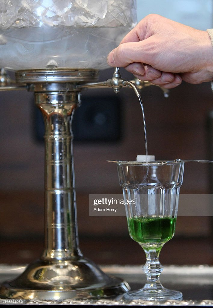Martial Philippi owner of the Absinth Depot shop uses an absinthe fountain to pour water through a sugar cube atop an absinthe spoon sitting on a...