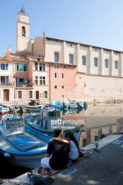 Martigues France A young couple sits on the 'Quai Aristide Briand' and look at the 'Quai Francois Marceau' in MartiguesMartigues is a commune in the...