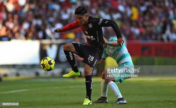 Martin Barragan of Atlas vies for the ball with Jorge Sanchez of Santos during their Mexican Clausura 2017 tournament football match at Jalisco...