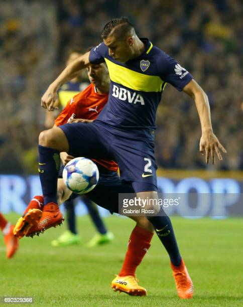 Martin Benitez of Independiente fights for the ball with Fernando Tobio of Boca Juniors during a match between Boca Juniors and Independiente as part...