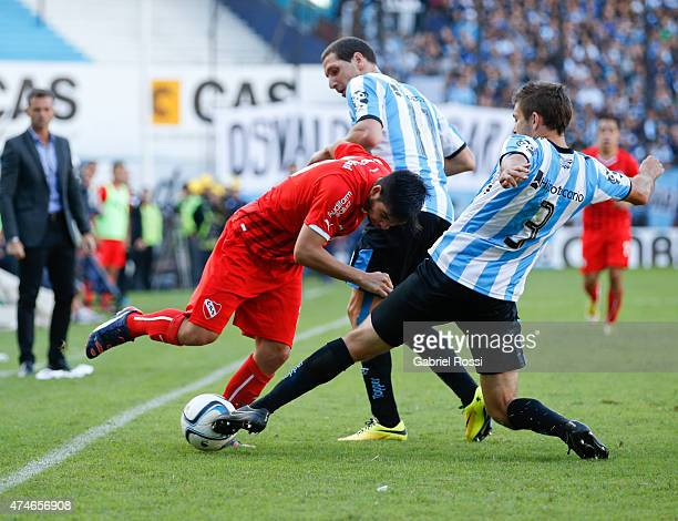 Martin Benitez of Independiente fights for the ball with Leandro Grimi of Racing Club during a match between Racing Club and Independiente as part of...