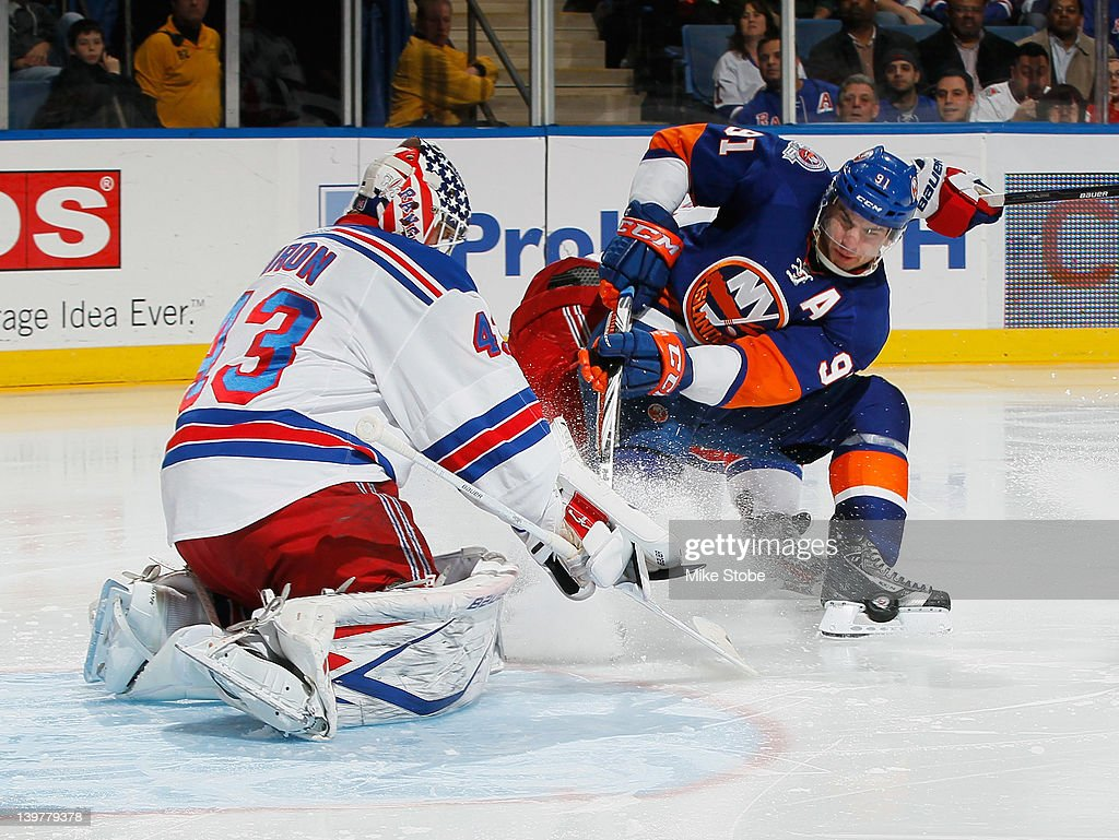 <a gi-track='captionPersonalityLinkClicked' href=/galleries/search?phrase=Martin+Biron&family=editorial&specificpeople=203146 ng-click='$event.stopPropagation()'>Martin Biron</a> #43 of the New York Rangers defends the net against <a gi-track='captionPersonalityLinkClicked' href=/galleries/search?phrase=John+Tavares&family=editorial&specificpeople=601791 ng-click='$event.stopPropagation()'>John Tavares</a> #91 of the New York Islanders at Nassau Veterans Memorial Coliseum on February 24, 2012 in Uniondale, New York.