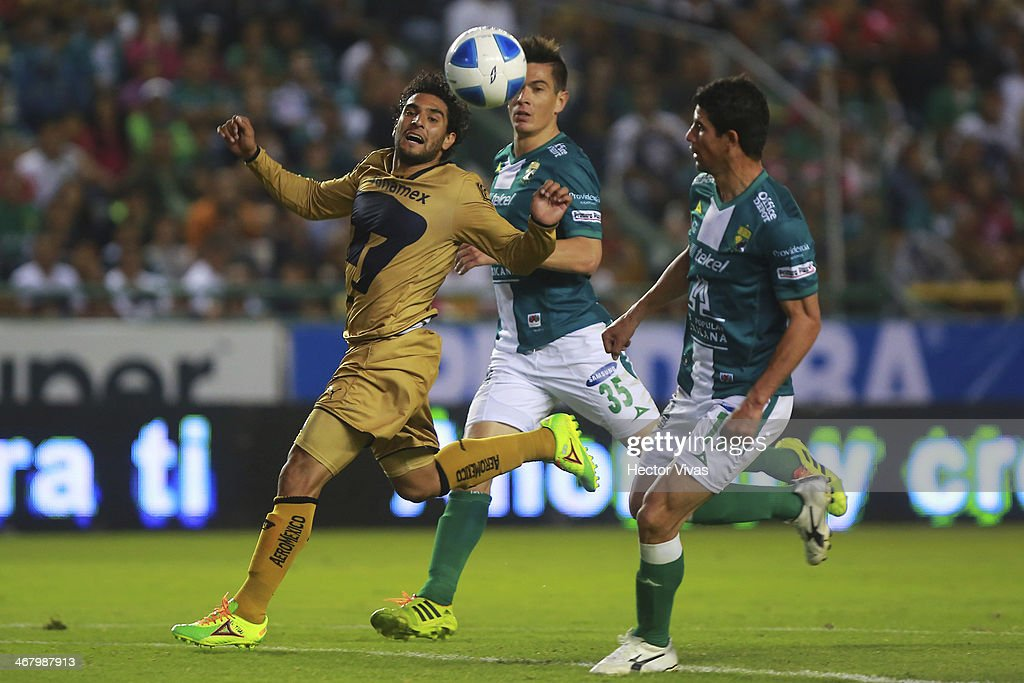 Martin Bravo of Pumas struggles for the ball with Jonny Magallon and Ignacio Gonzalez of Leon during a match between Leon and Pumas UNAM as part of...