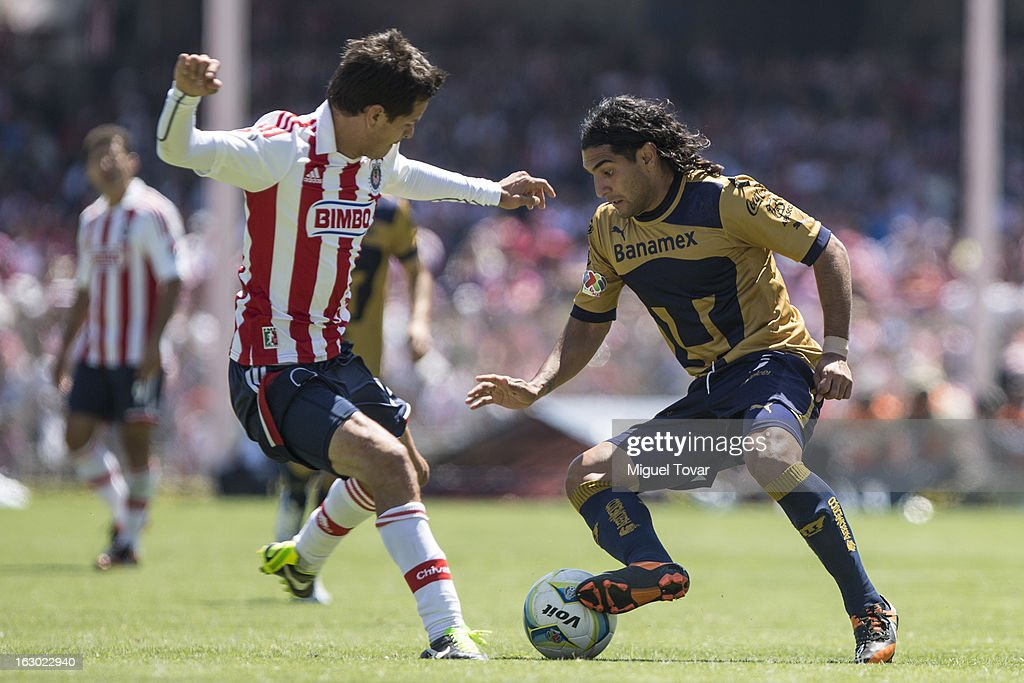 Martin Bravo (R) of Pumas struggles for the ball with Luis Morales (L) of Chivas during a match between Pumas and Chivas as part of Clausura 2013 Liga MX at Olympic Stadium on March 03, 2013 in Mexico City, Mexico.