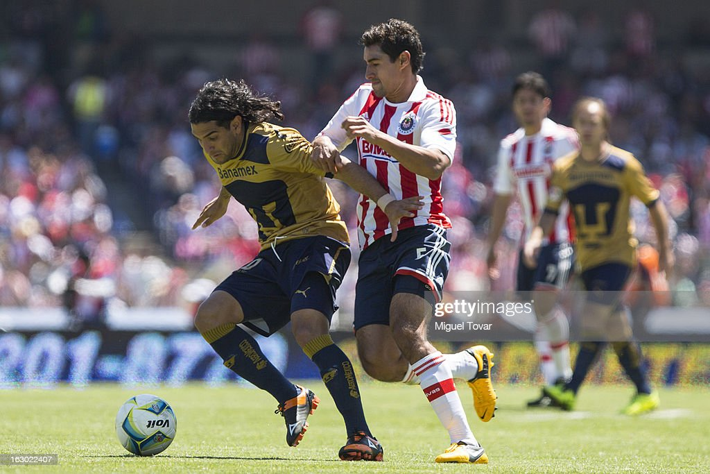 Martin Bravo (L) of Pumas struggles for the ball with Patricio Araujo (R) of Chivas during a match between Pumas and Chivas as part of Clausura 2013 Liga MX at Olympic Stadium on March 03, 2013 in Mexico City, Mexico.