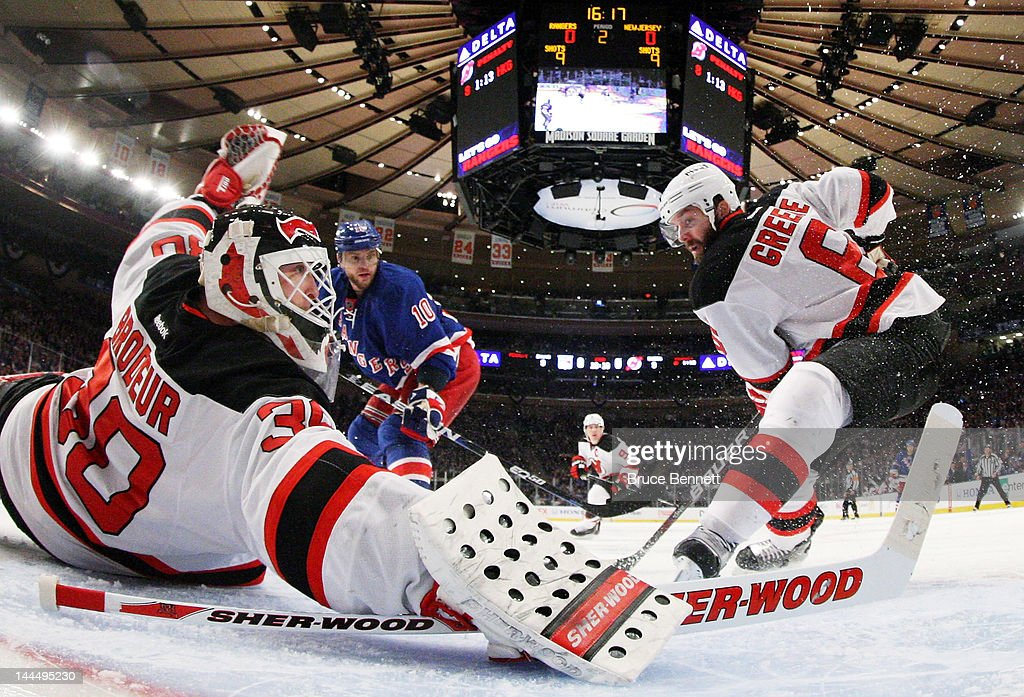 Martin Brodeur and Andy Greene of the New Jersey Devils defend against the New York Rangers in Game One of the Eastern Conference Final during the...