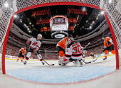 Martin Brodeur and Colin White of the New Jersey Devils defend against the attack of Jeff Carter and Danny Briere of the Philadelphia Flyers in Game...