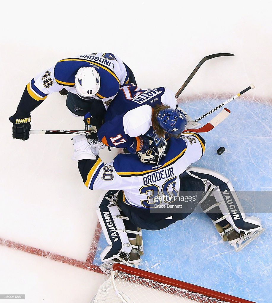 Martin Brodeur and Petteri Lindbohm of the St Louis Blues defend the net against Matt Martin of the New York Islanders during the third period at the...