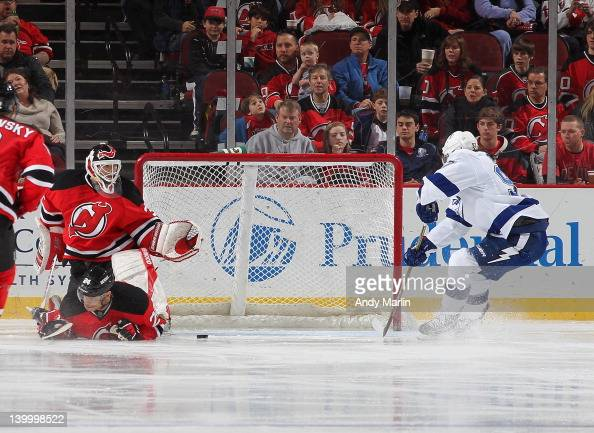 Martin Brodeur of the New Jersey Devils can't recover as Matt Gilroy of the Tampa Bay Lightning puts the puck in the net for a goal during the game...