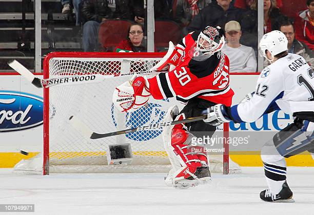 Martin Brodeur of the New Jersey Devils clears the puck from in front of Simon Gagne of the Tampa Bay Lightning in the second period of an NHL hockey...