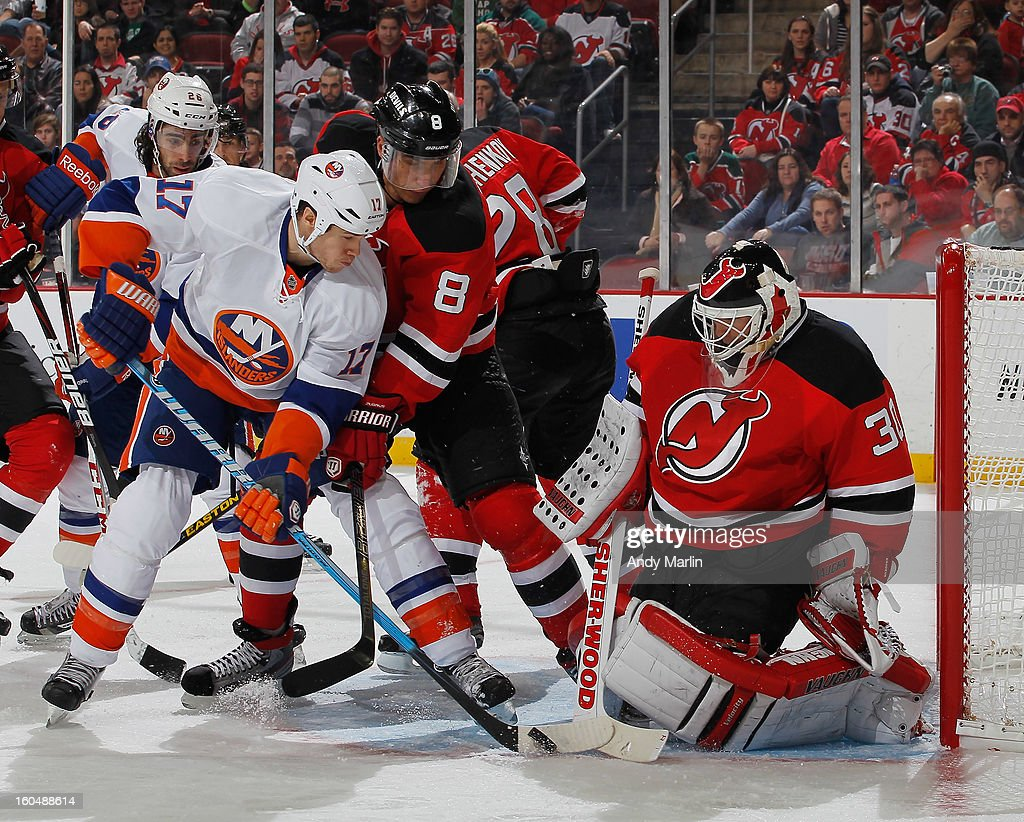 Martin Brodeur #30 of the New Jersey Devils defends his net as Dainius Zubrus #8 checks Matt Martin #17 of the New York Islanders during the game at the Prudential Center on January 31, 2013 in Newark, New Jersey.