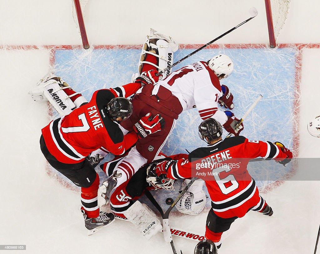 <a gi-track='captionPersonalityLinkClicked' href=/galleries/search?phrase=Martin+Brodeur&family=editorial&specificpeople=201594 ng-click='$event.stopPropagation()'>Martin Brodeur</a> #30 of the New Jersey Devils defends his net as <a gi-track='captionPersonalityLinkClicked' href=/galleries/search?phrase=Mark+Fayne&family=editorial&specificpeople=4008109 ng-click='$event.stopPropagation()'>Mark Fayne</a> #7 and <a gi-track='captionPersonalityLinkClicked' href=/galleries/search?phrase=Andy+Greene&family=editorial&specificpeople=3568726 ng-click='$event.stopPropagation()'>Andy Greene</a> #6 make contact with Martin Hanzal #11 of the Phoenix Coyotes at the Prudential Center on March 27, 2014 in Newark, New Jersey. The Coyotes defeated the Devils 3-2.