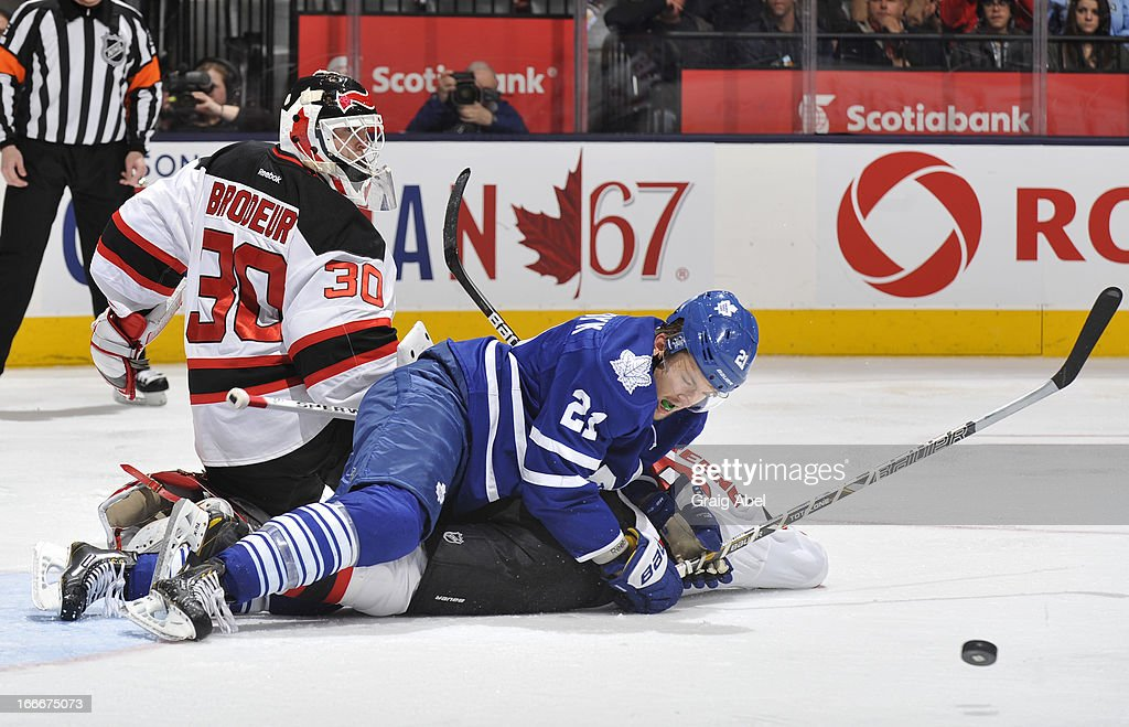 <a gi-track='captionPersonalityLinkClicked' href=/galleries/search?phrase=Martin+Brodeur&family=editorial&specificpeople=201594 ng-click='$event.stopPropagation()'>Martin Brodeur</a> #30 of the New Jersey Devils defends the goal as teammate <a gi-track='captionPersonalityLinkClicked' href=/galleries/search?phrase=Andy+Greene&family=editorial&specificpeople=3568726 ng-click='$event.stopPropagation()'>Andy Greene</a> #6 battls with James van Riemsdyk #21 of the Toronto Maple Leafs during NHL game action April 15, 2013 at the Air Canada Centre in Toronto, Ontario, Canada.
