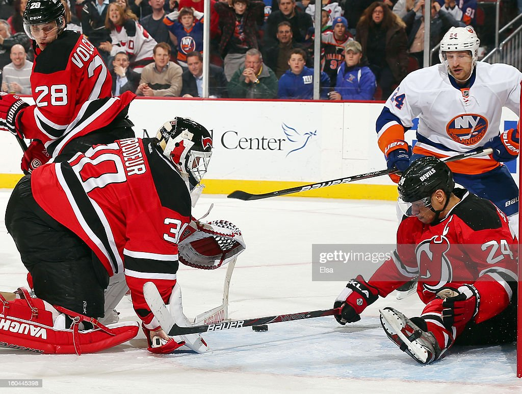 Martin Brodeur #30 of the New Jersey Devils is caught out of position as teammate Bryce Salvador #24 tries to stop the puck at the Prudential Center on January 31, 2013 in Newark, New Jersey. Brad Boyes #24 of the New York Islanders grabbed the rebound and scored the game winner. The New York Islanders defeated the New Jersey Devils 5-4 in overtime.