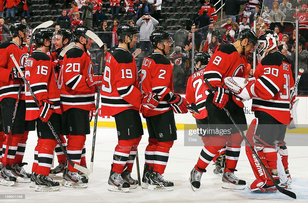 <a gi-track='captionPersonalityLinkClicked' href=/galleries/search?phrase=Martin+Brodeur&family=editorial&specificpeople=201594 ng-click='$event.stopPropagation()'>Martin Brodeur</a> #30 of the New Jersey Devils is congratulated by <a gi-track='captionPersonalityLinkClicked' href=/galleries/search?phrase=Dainius+Zubrus&family=editorial&specificpeople=204779 ng-click='$event.stopPropagation()'>Dainius Zubrus</a> #8 and the rest of this teammates after he shut out the Philadelphia Flyers during the season opener at the Prudential Center on January 22, 2013 in Newark, New Jersey.The New Jersey Devils shut out the Philadelphia Flyers 3-0.