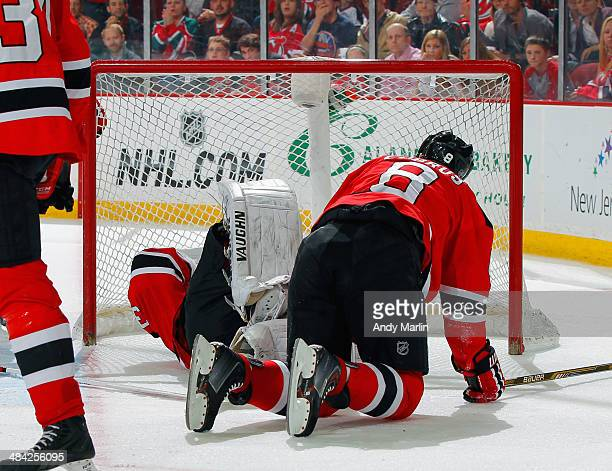 Martin Brodeur of the New Jersey Devils lies on the ice after being knocked down by teammate Dainius Zubrus during the game against the New York...