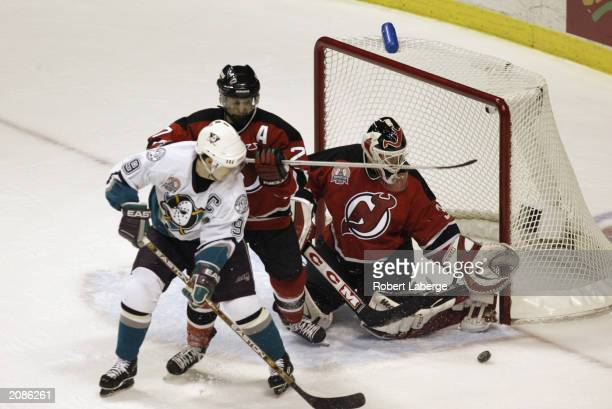 Martin Brodeur of the New Jersey Devils looks to make a save on Paul Kariya of the Mighty Ducks of Anaheim as Scott Niedermayer helps defend in game...