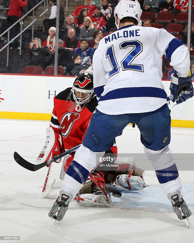 Martin Brodeur #30 of the New Jersey Devils makes a first period save under pressure from Ryan Malone #12 of the Tampa Bay Lightning at the Prudential Center on February 7, 2013 in Newark, New Jersey.