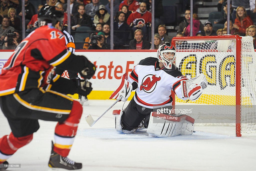 <a gi-track='captionPersonalityLinkClicked' href=/galleries/search?phrase=Martin+Brodeur&family=editorial&specificpeople=201594 ng-click='$event.stopPropagation()'>Martin Brodeur</a> #30 of the New Jersey Devils makes a glove save against the shot of <a gi-track='captionPersonalityLinkClicked' href=/galleries/search?phrase=Lance+Bouma&family=editorial&specificpeople=4303790 ng-click='$event.stopPropagation()'>Lance Bouma</a> #17 of the Calgary Flames during an NHL game at Scotiabank Saddledome on October 11, 2013 in Calgary, Alberta, Canada. The Calgary Flames defeated the New Jersey Devils 3-2.