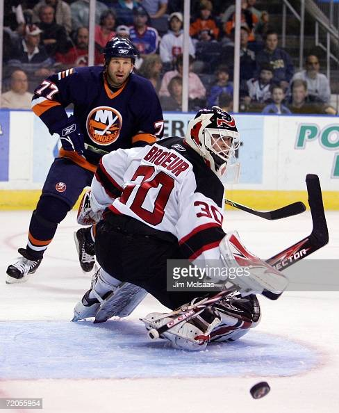 Martin Brodeur of the New Jersey Devils makes a save as Alexei Zhitnik of the New York Islanders looks on during their NHL pre season game on...
