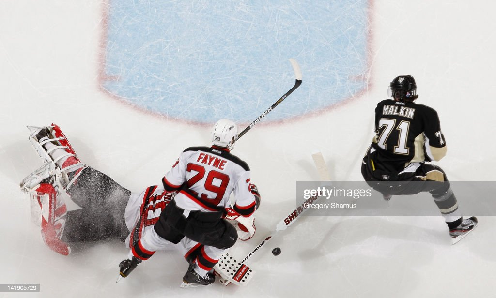 <a gi-track='captionPersonalityLinkClicked' href=/galleries/search?phrase=Martin+Brodeur&family=editorial&specificpeople=201594 ng-click='$event.stopPropagation()'>Martin Brodeur</a> #30 of the New Jersey Devils makes a save on <a gi-track='captionPersonalityLinkClicked' href=/galleries/search?phrase=Evgeni+Malkin&family=editorial&specificpeople=221676 ng-click='$event.stopPropagation()'>Evgeni Malkin</a> #71 of the Pittsburgh Penguins in front of Mark Fayne #29 on March 25, 2012 at Consol Energy Center in Pittsburgh, Pennsylvania.