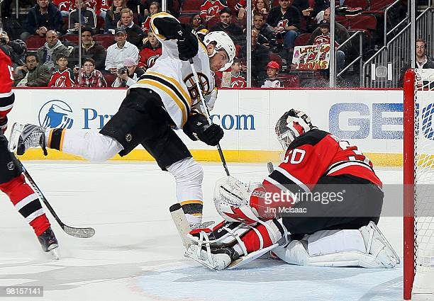Martin Brodeur of the New Jersey Devils makes an overtime save against Mark Recchi of the Boston Bruins at the Prudential Center on March 30 2010 in...