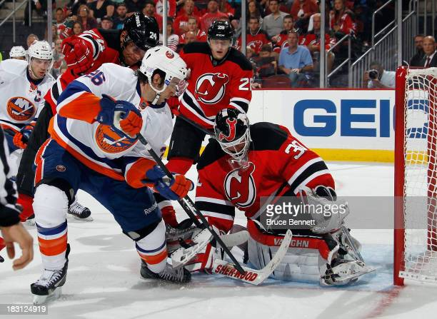 Martin Brodeur of the New Jersey Devils makes the third period save on Matt Moulson of the New York Islanders at the Prudential Center on October 4...