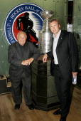 Martin Brodeur of the New Jersey Devils poses in front of the Stanley Cup with his father Denis at the launching of 'Brodeur Beyond the Crease' in...