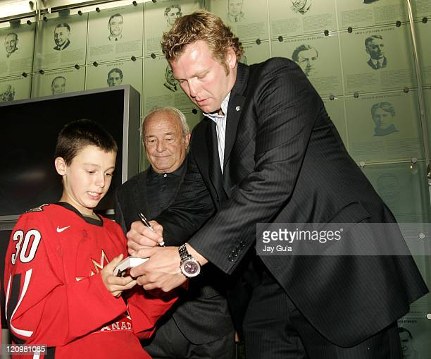 Martin Brodeur of the New Jersey Devils signs a copy of his new book for a fan as his father Denis looks on at the launching of 'Brodeur Beyond the...