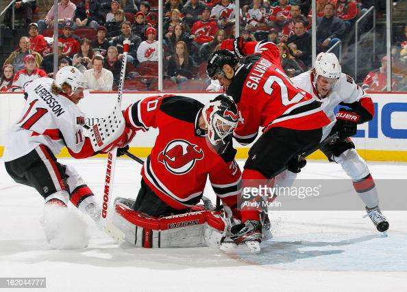 Martin Brodeur of the New Jersey Devils turns and makes a save as Bryce Salvador battles for the rebound in the crease against Daniel Alfredsson and...