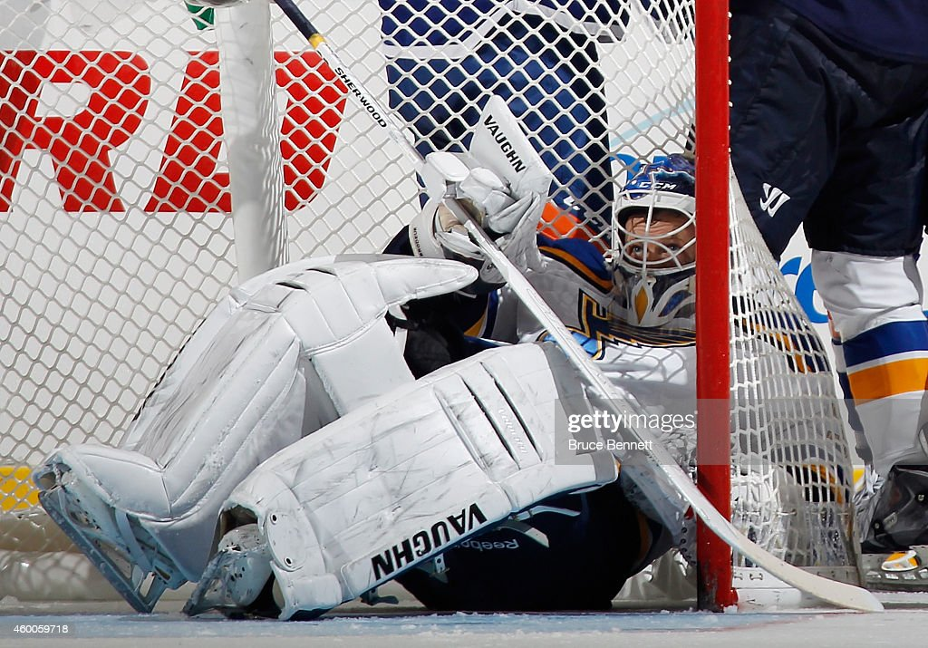 Martin Brodeur of the St Louis Blues gets knocked into the net during the third period against the New York Islanders at the Nassau Veterans Memorial...