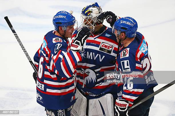Martin Buchwieser goalkeeper Dennis Endras and James Sifers of Mannheim celebrate after the DEL match between Adler Mannheim and Straubing Tigers at...