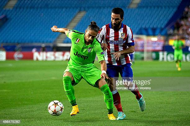 Martin Caceres of Juventus competes for the ball with Arda Turan of Atletico de Madrid during the UEFA Champions League group A match between Club...