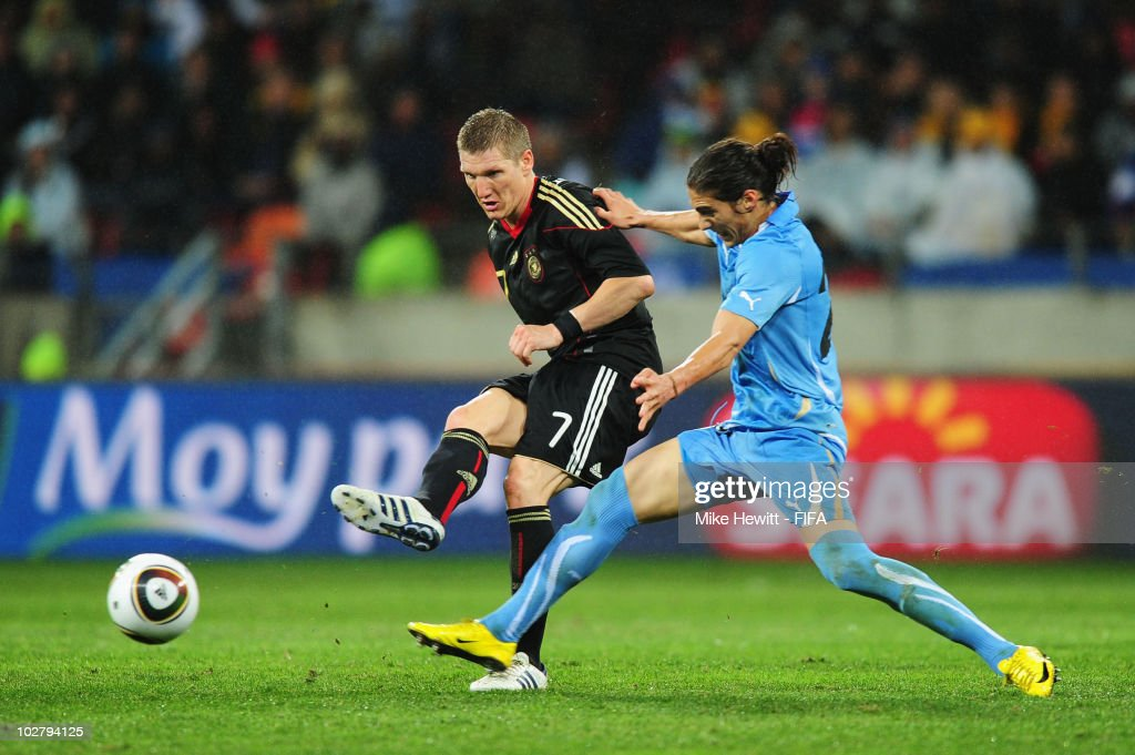 Martin Caceres of Uruguay attempts to tackle Bastian Schweinsteiger of Germany during the 2010 FIFA World Cup South Africa Third Place Play-off match between Uruguay and Germany at The Nelson Mandela Bay Stadium on July 10, 2010 in Port Elizabeth, South Africa.
