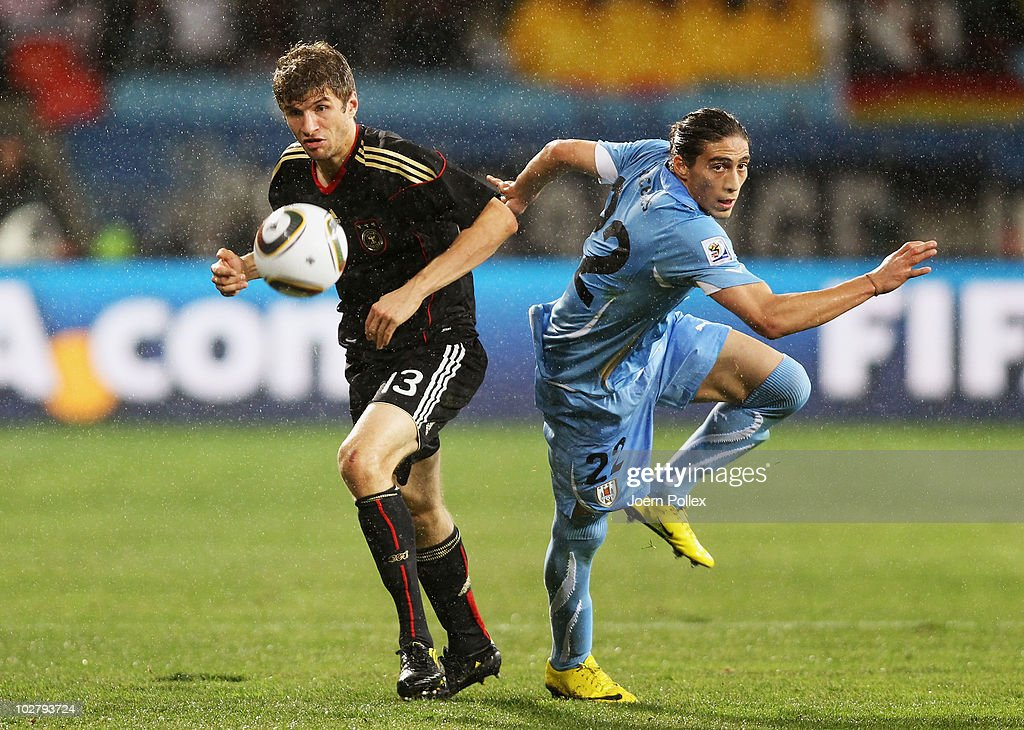 Martin Caceres of Uruguay competes for the ball with Thomas Mueller of Germany during the 2010 FIFA World Cup South Africa Third Place Playoff match...