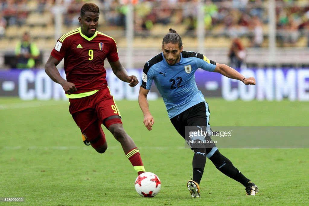 Martin Caceres of Uruguay drives the ball while followed by Sergio Cordova of Venezuela during a match between Venezuela and Uruguay as part of FIFA 2018 World Cup Qualifiers at Pueblo Nuevo Stadium on October 05, 2017 in San Cristobal, Venezuela.