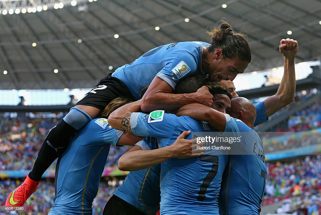 Martin Caceres of Uruguay piles on his teammates celebrating the team's first goal on a penalty kick by <a gi-track='captionPersonalityLinkClicked' href=/galleries/search?phrase=Edinson+Cavani&family=editorial&specificpeople=4104253 ng-click='$event.stopPropagation()'>Edinson Cavani</a> (obscured) on during the 2014 FIFA World Cup Brazil Group D match between Uruguay and Costa Rica at Castelao on June 14, 2014 in Fortaleza, Brazil.