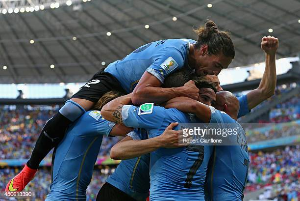 Martin Caceres of Uruguay piles on his teammates celebrating the team's first goal on a penalty kick by Edinson Cavani on during the 2014 FIFA World...