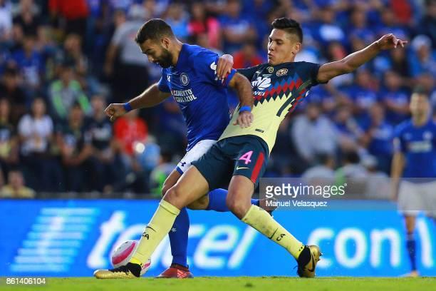 Martin Cuateruccio of Cruz Azul struggles for the ball against Edson Alvarez of America during the 13th round match between Cruz Azul and America as...
