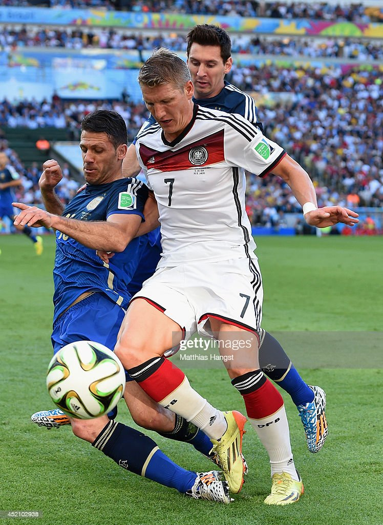Martin Demichelis (L) and Lionel Messi of Argentina challenge Bastian Schweinsteiger of Germany during the 2014 FIFA World Cup Brazil Final match between Germany and Argentina at Maracana on July 13, 2014 in Rio de Janeiro, Brazil.